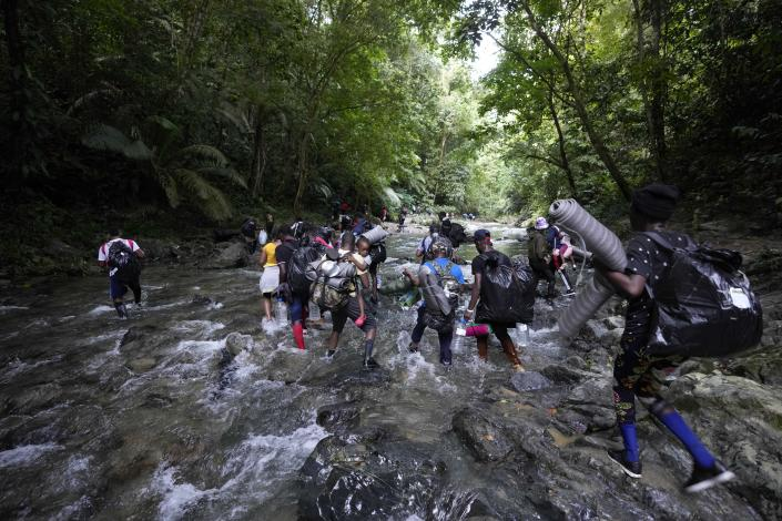 Migrants cross the Acandi River on their journey north, near Acandi, Colombia, Wednesday, Sept. 15, 2021. The migrants, mostly Haitians, are on their way to crossing the Darien Gap from Colombia into Panama dreaming of reaching the U.S. (AP Photo/Fernando Vergara)