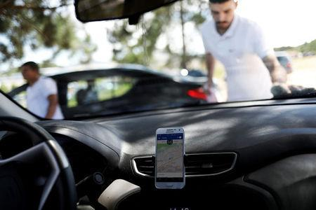 An Uber driver cleans his car as his cell phone shows the queue to pick up passengers departing Guarulhos International Airport in Sao Paulo, Brazil, February 13, 2017. REUTERS/Nacho Doce