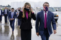 FILE- In this July 15, 2020, file photo Sen. Kelly Loeffler, R-Ga., puts on a face mask as she walks with Sen. David Perdue, R-Ga., right, at UPS Hapeville Airport Hub in Atlanta. (AP Photo/Evan Vucci, File)