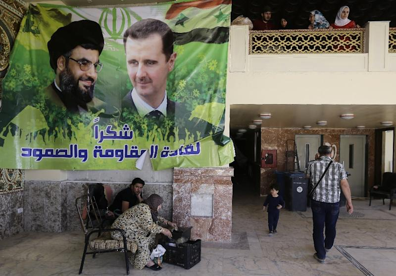 Syrians gather in the lobby of a damaged apartment block, bearing a poster of Syrian President Bashar al-Assad (R) and Hassan Nasrallah, south of the Syrian capital Damascus on April 25, 2016