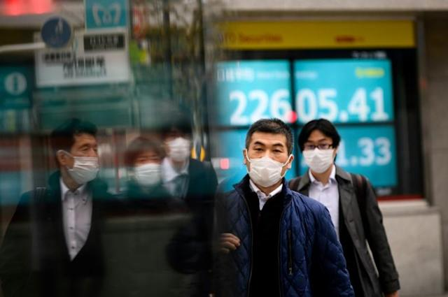 Infections of the new coronavirus have spiked inside Japan, where Tokyo pedestrians are pictured wearing face masks (AFP Photo/Philip FONG)