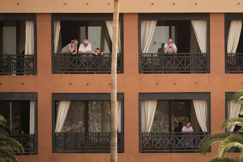 People stand on their balconies of the H10 Costa Adeje Palace hotel in the Canary Island of Tenerife, Spain, Tuesday, Feb. 25, 2020. Spanish officials say a tourist hotel on the Canary Island of Tenerife has been placed in quarantine after an Italian doctor staying there tested positive for the COVID-19 virus and Spanish news media says some 1,000 tourists staying at the complex are not allowed to leave. (AP Photo) (Photo: ASSOCIATED PRESS)