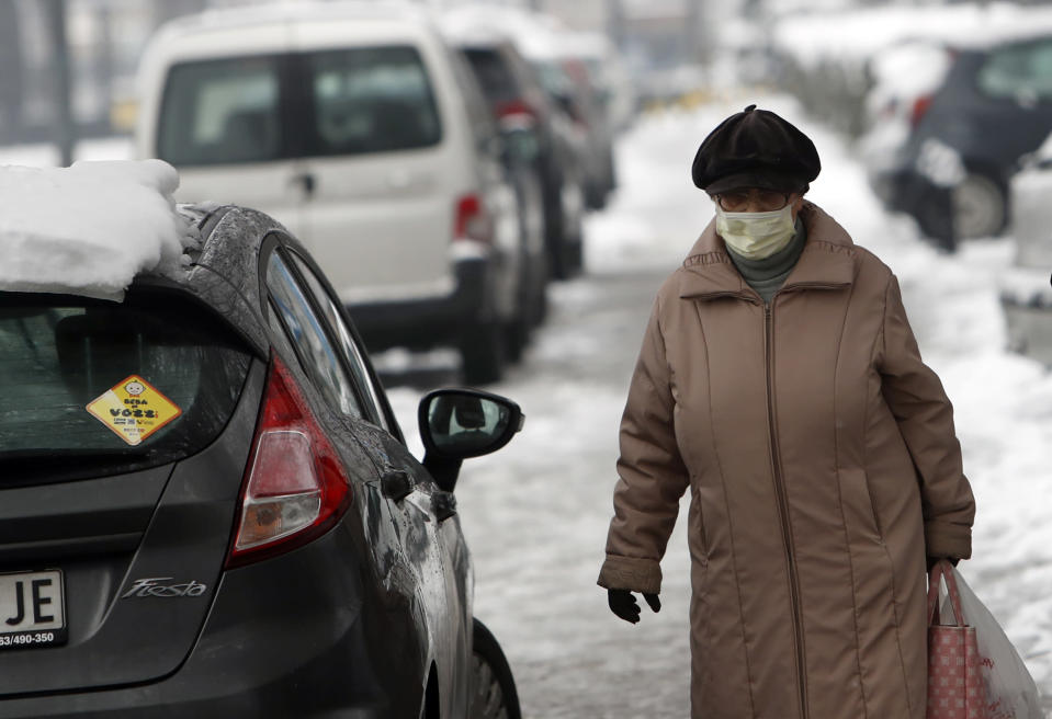 A woman wearing a face mask to protect against coronavirus walks through the snow covered street in Belgrade, Serbia, Monday, Jan. 11, 2021. A spate of rainy and snowy weather across the Balkans in the past days has left homes and fields flooded, disrupted road and sea traffic and caused power outages. (AP Photo/Darko Vojinovic)