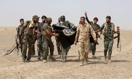 Iraq's Shi'ite paramilitaries and members of Iraqi security forces hold an Islamist State flag which they pulled down in Nibai, in Anbar province May 26, 2015. REUTERS/Stringer