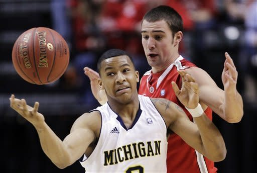 Michigan guard Trey Burke (3) battles for a loose ball against Ohio State guard Aaron Craft (4) in the first half of an NCAA college basketball game in the semifinals of the Big Ten Conference tournament in Indianapolis, Saturday, March 10, 2012. (AP Photo/Michael Conroy)