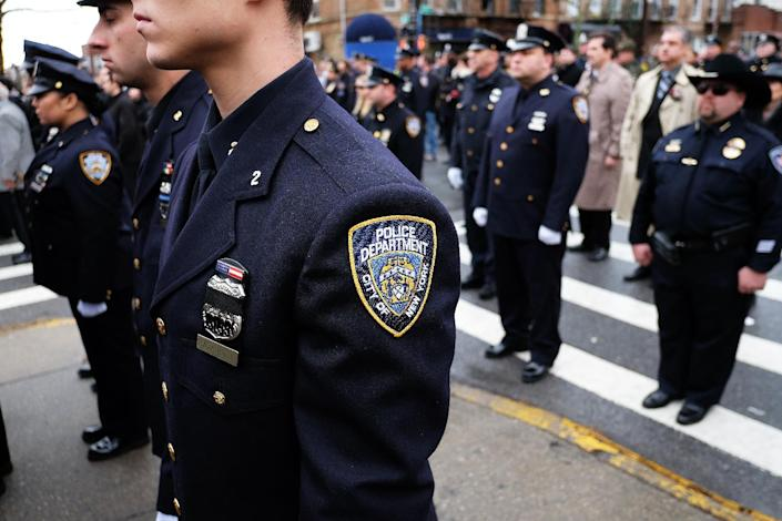 New York Police Department officers pay their respects as the procession of their fellow officer Wenjian Liu passes by in New York's borough of Brooklyn on January 4, 2015 (AFP Photo/Jewel Samad)