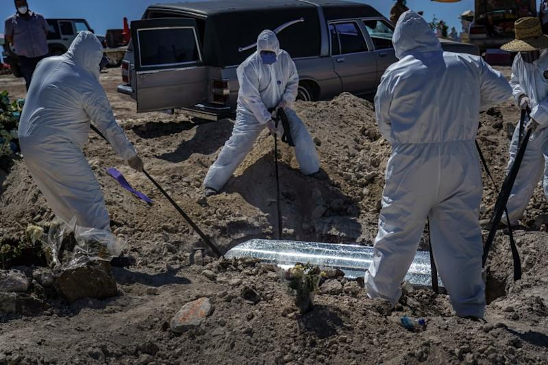 TIJUANA, BAJA CALIFORNIA -- SATURDAY, APRIL 25, 2020: Workers in protective suits lower a coffin carrying Laura Moreno Sanche, 49, who passed away due to COVID-19, towards a new crop of graves that are set aside for COVID-19 victims alongside other victims of violence and other diseases, at the municipal pantheon number 13 cemetery, in Tijuana, Mexico, on April 25, 2020. Not pictured, are her family members and friends watching the burial at a safe distance. (Marcus Yam / Los Angeles Times)