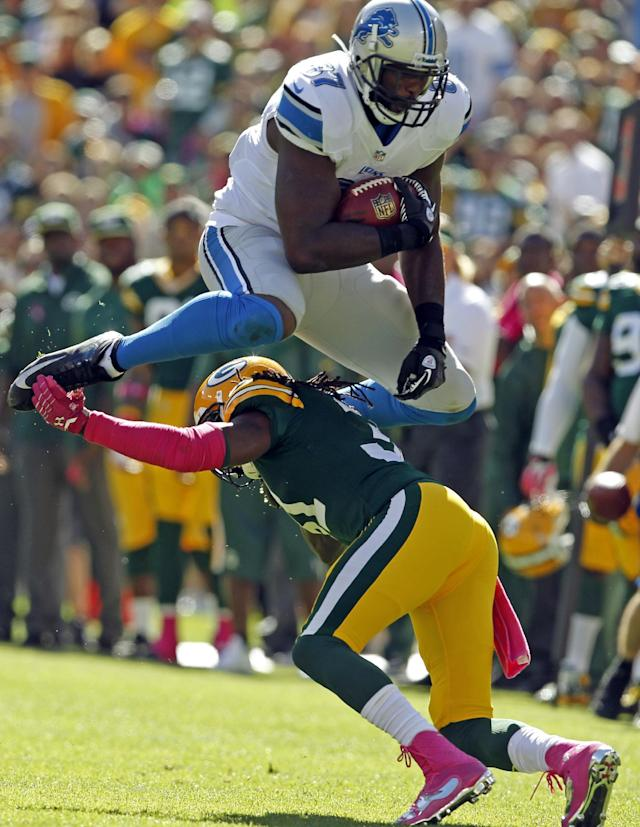Detroit Lions' Brandon Pettigrew tries to leap over Green Bay Packers' Davon House after a catch during the first half of an NFL football game Sunday, Oct. 6, 2013, in Green Bay, Wis. (AP Photo/Mike Roemer)