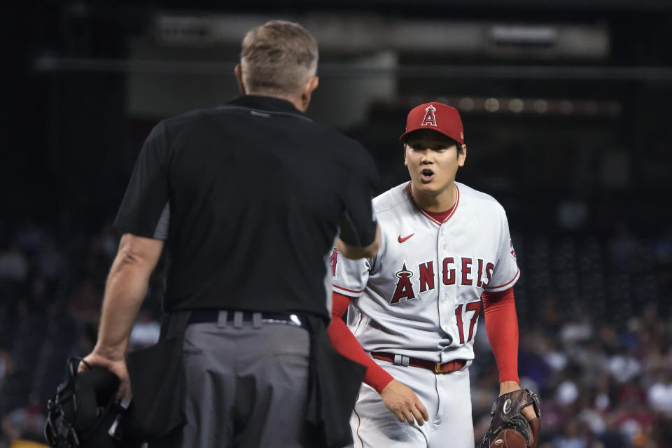Los Angeles Angels pitcher Shohei Ohtani (17) talks tumpire Greg Gibson after getting called for his second balk, in the fifth inning of the team's baseball game against the Arizona Diamondbacks, Friday, June 11, 2021, in Phoenix. (AP Photo/Rick Scuteri)