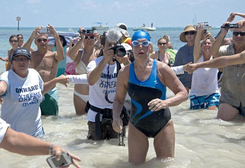 FILE - In this Monday, Sept. 2, 2013 file photo provided by the Florida Keys News Bureau, Diana Nyad emerges from the Atlantic Ocean after completing a 111-mile swim from Cuba to Key West, Fla. Nyad's swim from Cuba to Florida has generated some skepticism in the small community of marathon swimmers. Critics have suggested that during a speedy stretch of the 53-hour swim, Nyad might have gotten into or held onto the boat that accompanied her. They also question whether she violated the traditions of her sport by relying on a specialized mask and wetsuit to protect herself from jellyfish. Nyad's navigator and one of the swim's official observers tell The Associated Press that Nyad didn't cheat. (AP Photo/Florida Keys Bureau, Andy Newman, File)