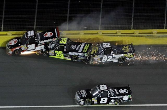 Ron Hornaday Jr. (30), Mason Mingus (35) and Jake Crum (82) collide in Turn 3 as Joe Nemeckek (8) drives low during the NASCAR Truck series auto race in Concord, N.C., Friday, May 16, 2014. (AP Photo/Gerry Broome)