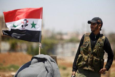 FILE PHOTO: A Syrian army soldier stands next to a Syrian flag in Umm al-Mayazen, in the countryside of Deraa