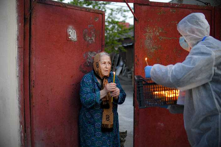 An elderly woman receives Holy Light from a volunteer in Bucharest, Romania, Saturday, April 18, 2020. Priests accompanied by volunteers distributed the candles ahead of the usual time, at midnight, as people observed the ban on gatherings in the week leading to the Orthodox Easter, as authorities try to limit the spread of the COVID-19 coronavirus. (AP Photo/Andreea Alexandru)