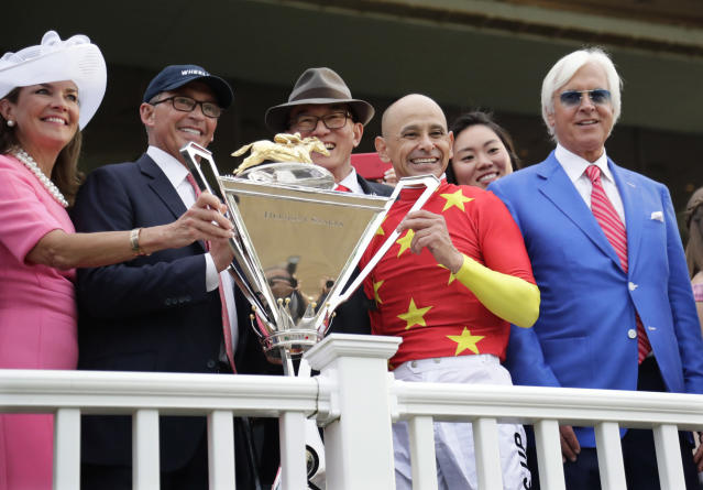 FILE - In this June 9, 2018, file photo, jockey Mike Smith, second from right, trainer Bob Baffert, right, and owners Kenny Trout, second from left, and Teo Ah Khing pose with the Triple Crown trophy after race horse Justify won the 150th running of the Belmont Stakes horse race, at Belmont Park in Elmont, N.Y. The Belmont Stakes will be run June 20, 2020, without fans and serve as the opening leg of horse racing's Triple Crown for the first time in the sport's history. The New York Racing Association on Tuesday, May 19, 2020, unveiled the rescheduled date for the Belmont, which will also be contested at a shorter distance than usual. This is the first time the Belmont will lead off the Triple Crown ahead of the Kentucky Derby and Preakness. (AP Photo/Frank Franklin II, File)