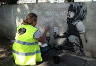 Martha Swabey from Fine Art Restoration Company cleaning the artwork before a protective case is placed around the Banksy mural, which appeared following Extinction Rebellion climate change protests on Marble Arch, London, to preserve it for the future.