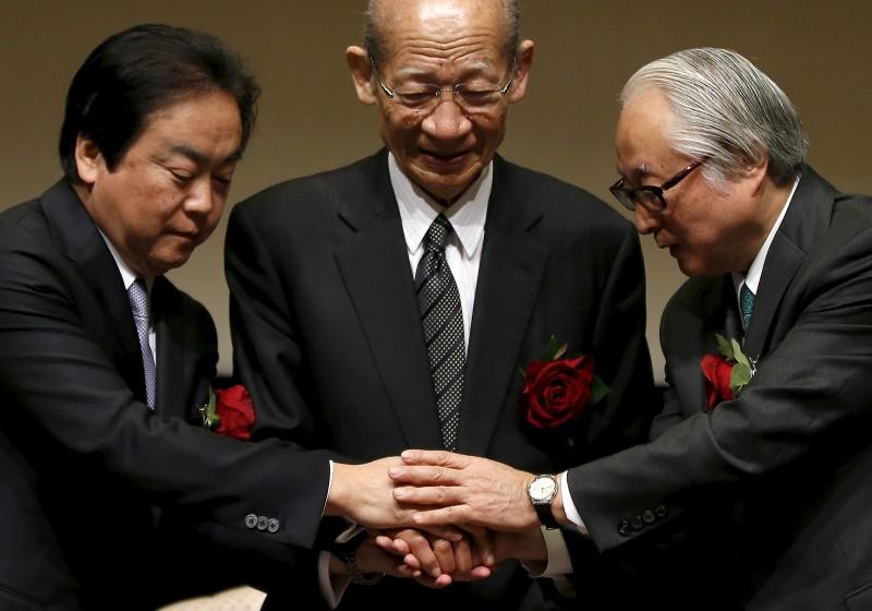 Japan Post Holdings Co President Nishimuro, Japan Post Bank Co President Nagato and Japan Post Insurance Co President Ishii shake hands during joint news conference after ceremony to mark company's debut on Tokyo Stock Exchange