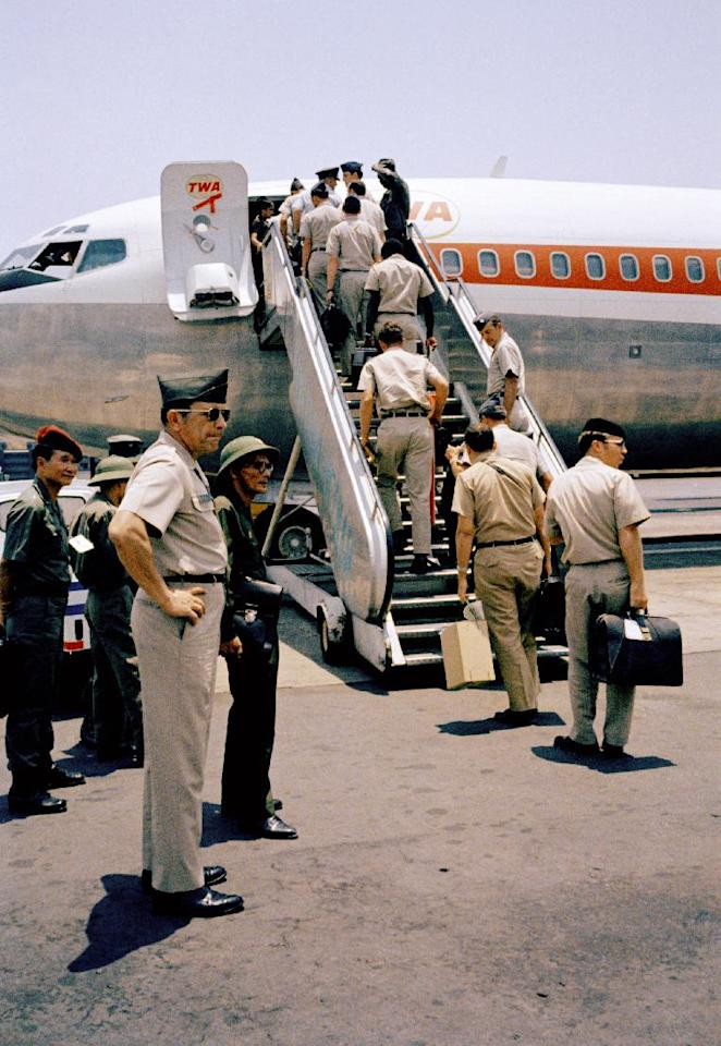 In this March 29, 1973 photo, In a curious ending to a bizarre conflict, American troops board jets under the watchful eyes of North Vietnamese and Viet Cong observers in Saigon. As the last U.S. combat troops left Vietnam 40 years ago, angry protesters still awaited them at home. North Vietnamese soldiers took heart from their foes' departure, and South Vietnamese who had helped the Americans feared for the future. While the fall of Saigon two years later — with its indelible images of frantic helicopter evacuations — is remembered as the final day of the Vietnam War, Friday marks an anniversary that holds greater meaning for many who fought, protested or otherwise lived it. (AP Photo)