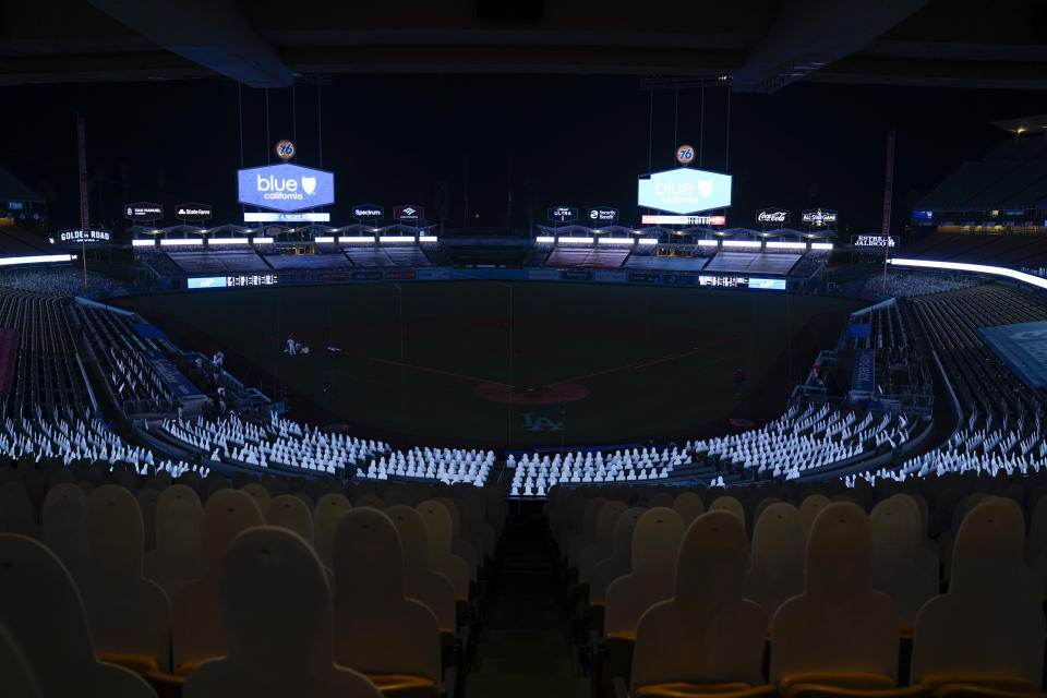 Players leave the field after a power outage during the seventh inning of a baseball game between the Los Angeles Angels and the Los Angeles Dodgers, Saturday, Sept. 26, 2020, in Los Angeles. (AP Photo/Ashley Landis)