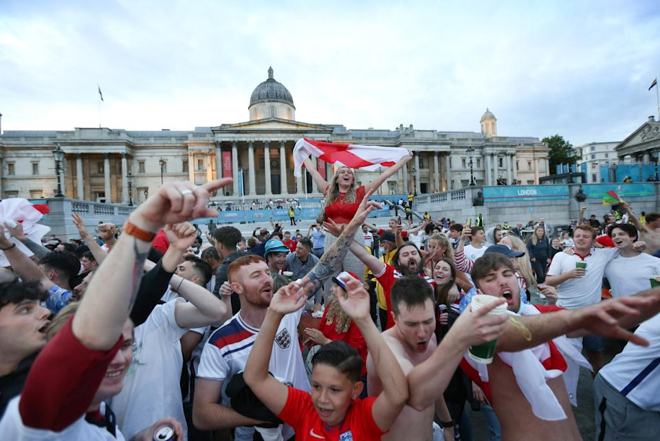 Covid-19 regulations are forgotten as England fans stand on their tables to celebrate as they watch the euro 2020 quarter final match between England and Ukraine from inside the Fan Zone set up to adhere to Covid-19 regulations in Trafalgar Square.