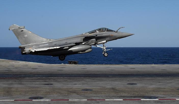 A French Rafale fighter aircraft carrying bombs is catapulted off aircraft carrier Charles-de-Gaulle at eastern Mediterranean Sea, as part of operation Chammal in Syria and Iraq against the Islamic State (IS) group on November 23, 2015 (AFP Photo/Anne-Christine Poujoulat)