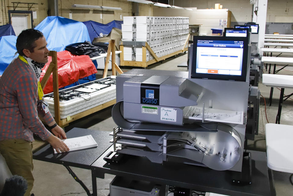 Allegheny County Election Division Deputy Manager Chet Harhut demonstrates a mail-in and absentee ballot counting machine at the Elections warehouse in Pittsburgh Monday, June 1, 2020. Pennsylvania holds its primary on Tuesday, June 2. (AP Photo/Gene J. Puskar)