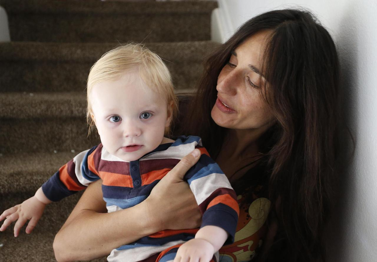 In this Thursday, Oct. 20, 2016 photo, vegan mother Fulvia Serra holds her 1-year-old son, Sebastiano, at home in Fort Collins, Colo. Serra, originally from Italy, and her husband, Scott, are raising their son vegan. Despite criticism and innuendo from some circles, pediatricians and nutritionists agree it's perfectly healthy to feed babies a vegan diet. However, parents need to be well-informed about the nutritional elements different foods offer, and work closely with their doctor or health care provider. (AP Photo/Brennan Linsley)