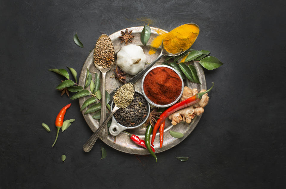 Flat lay overhead view herb and spices in vintage silver plate on textured black background. Asian or indian cuisine colourful spices close up image.