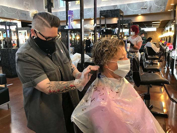 "Natascha Updegrove cuts client Karon Gilmore's hair on the first day that Georgia reopened salons, spas, gyms and bowling alleys. <span class=""copyright"">(Jenny Jarvie / Los Angeles Times)</span>"