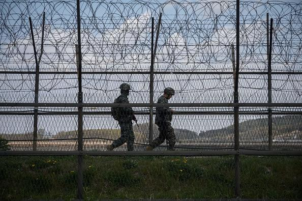 South Korean soldiers patrol along a barbed wire fence Demilitarised Zone (DMZ) separating North and South Korea, on the South Korean island of Ganghwa.