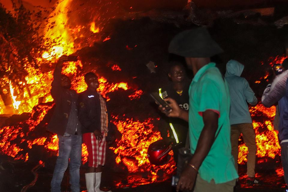 People stand and take selfies in front of lava from the eruption of Mount Nyiragongo, in Buhene, on the outskirts of GomaAP