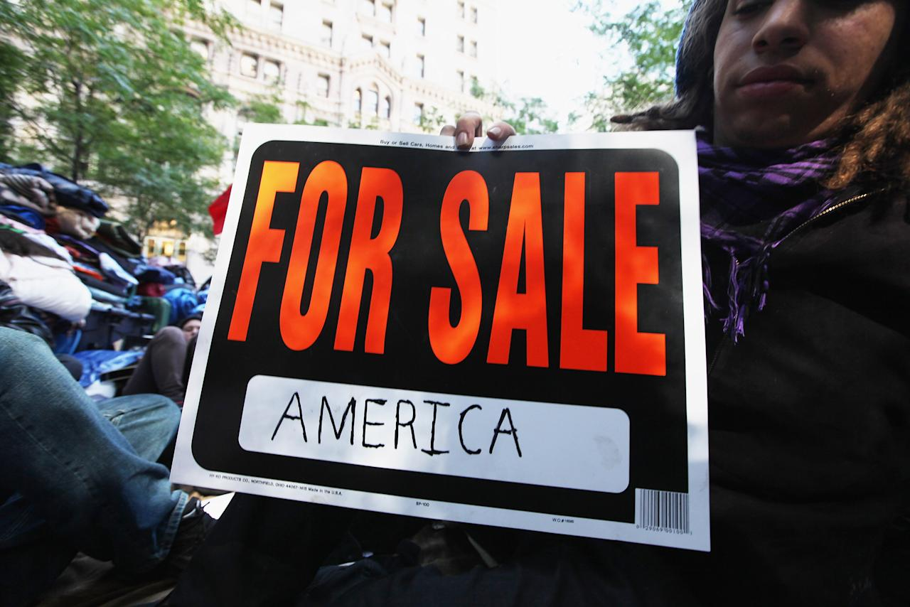 NEW YORK, NY - OCTOBER 05:   A protester affiliated with the Occupy Wall Street movement holds a sign before marching through Lower Manhattan on October 5, 2011 in New York City. Thousands of protesters including union members and college students from an organized walkout joined the rally and march.  (Photo by Mario Tama/Getty Images)