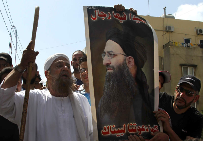 """Lebanese protesters hold a poster of hard-line Sunni cleric Sheik Ahmad al-Assir with the Arabic reading, """"There are men in Sidon. Anytime you call us we will respond,"""" and chant slogans against Hezbollah after the Friday prayer in the southern port city of Sidon, Lebanon, Friday, June 28, 2013. Lebanese troops have fired in the air to disperse dozens of Sunni Muslims demonstrating in support of a hard-line cleric who has been on the run since the military crushed his fighters earlier this week. (AP Photo/Mohammed Zaatari)"""