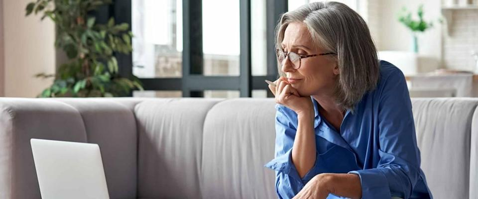 Senior mature older woman looking at laptop while sitting at a desk.