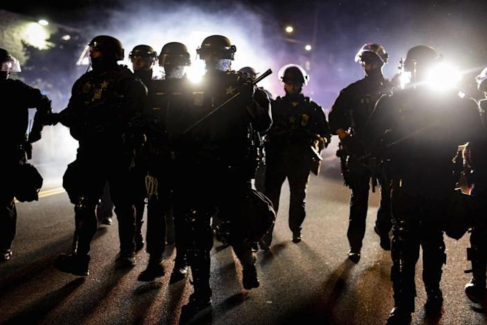 """In this Aug. 9, 2020 photo, Portland, Ore., police officers in riot gear advance on a group of protesters after a demonstration was declared an """"unlawful assembly."""" (Photo: Maranie Rae Staab via AP)"""