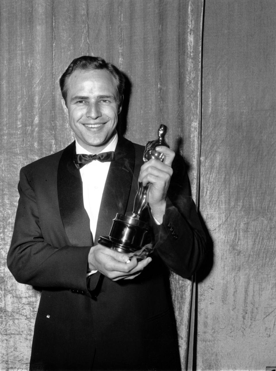 """Oscar-winner Marlon Brando poses with his statuette at the 27th Annual Academy Awards at Pantages Theater in Hollywood, Ca. on March 30, 1955.  Brando won best actor of the year for his portrayal in """"On the Waterfront.""""  (AP Photo)"""