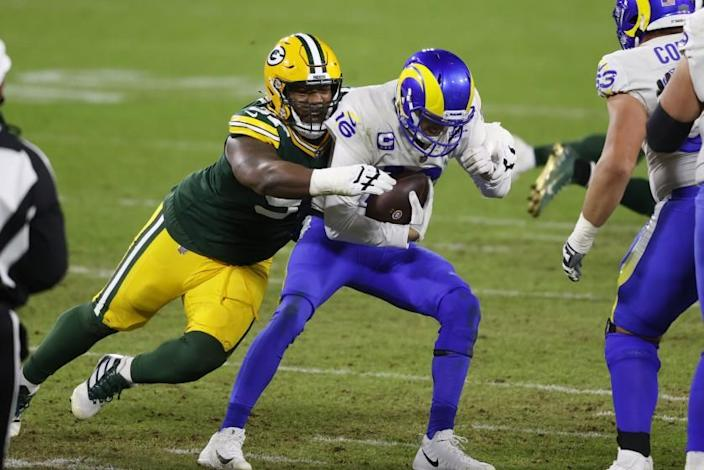 Green Bay Packers nose tackle Kenny Clark (97) sacks Los Angeles Rams quarterback Jared Goff (16) during an NFL divisional playoff football game between the Los Angeles Rams and Green Bay Packers, Saturday, Jan. 16, 2021, in Green Bay, Wis. (AP Photo/Jeffrey Phelps)