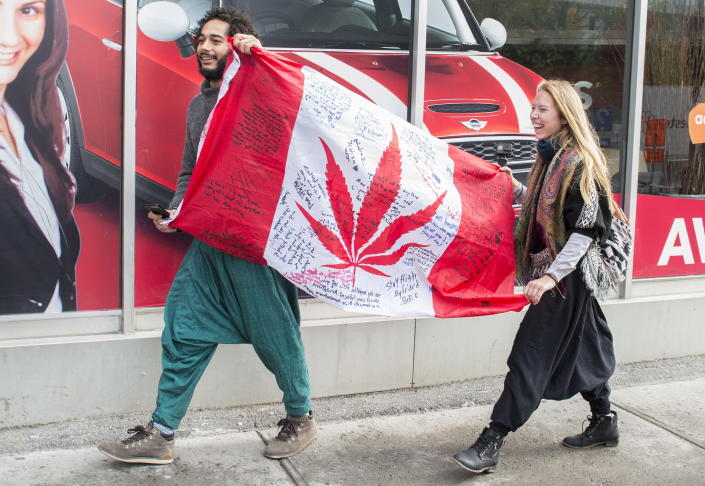 <p>People hold up a Canadian flag with a marijuana logo on it outside a government cannabis store in Montreal, Wednesday, Oct. 17, 2018. (Photo: Graham Hughes/The Canadian Press via AP) </p>