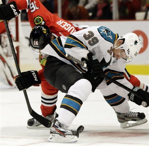 San Jose Sharks' Logan Couture (39) and Chicago Blackhawks' Marcus Kruger (16) battle for the puck during the first period of an NHL hockey game in Chicago, Friday, Feb. 22, 2013. (AP Photo/Nam Y. Huh)