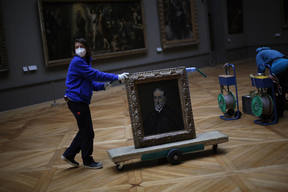 A worker transports the painting called 'Portrait of Antonio de Covarrubias y Leiva' by Spanish painter El Greco, in the Louvre museum, in Paris, Tuesday, Feb. 9, 2021. Though empty corridors and vacant galleries are a grim sight for frustrated art-lovers, they are a golden opportunity to do works of renovation, refurbishment and re-ordering that were simply not possible with the around 10 million visitors per year. (AP Photo/Thibault Camus)