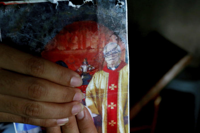 In this Jan. 25, 2019 photo, a resident holds an undated photograph of the town's Catholic parish priest Father Pius Hendricks, in Talustusan on Biliran Island in the central Philippines. (AP Photo/Bullit Marquez)