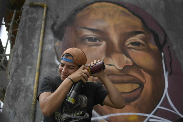 "Street artist Wolfgang Salazar mixes spray paint backdropped by his most recent art mural featuring Venezuelan athlete Yulimar Rojas, in the Boleita neighborhood of Caracas, Venezuela, Saturday, Jan. 2, 2021. Salazar uses the artistic name of Badsura, a play on the English word ""bad"" and the Spanish word ""basura,"" for ""garbage,"" (AP Photo/Matias Delacroix)"