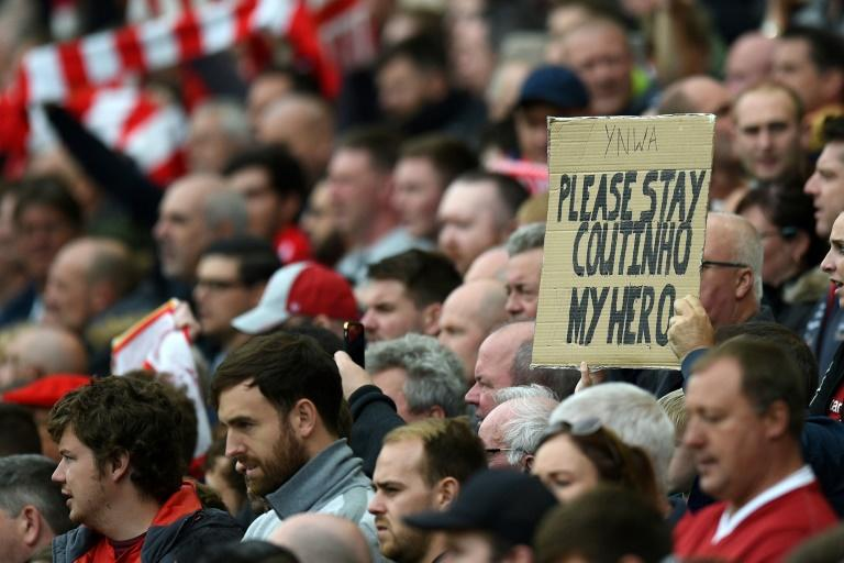 A fan holds up a placard in support of Liverpool's Brazilian midfielder Philippe Coutinho on August 19, 2017