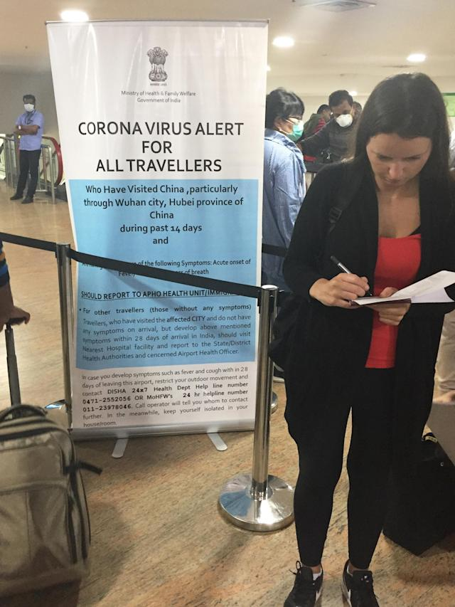 Foreign tourists complete declarations stating they have not recently traveled to China and that they are not experiencing any symptoms of the Wuhan coronavirus at Trivandrum International Airport in Kerala.