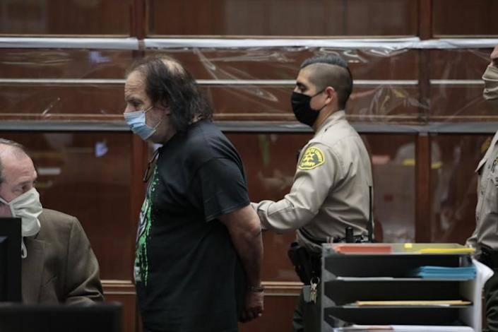 "Adult film star Ron Jeremy leaves a Los Angeles County courtroom in handcuffs after he was charged with four counts of sexual assault. <span class=""copyright"">(Robert Gauthier/Los Angeles Times)</span>"