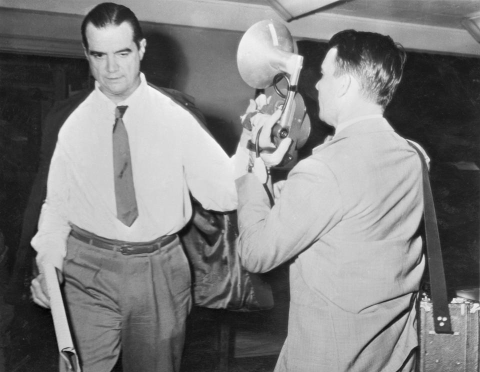 "(Original Caption) As he departed from the courtroom where Howard Hughes' left hand is apparently doing TV cameraman Harry Watson's camera no good. Hughes denies that he used the Paul Herrico incident to close down RKO Studios. ""That is a ridiculous assumption,"" says Hughes."