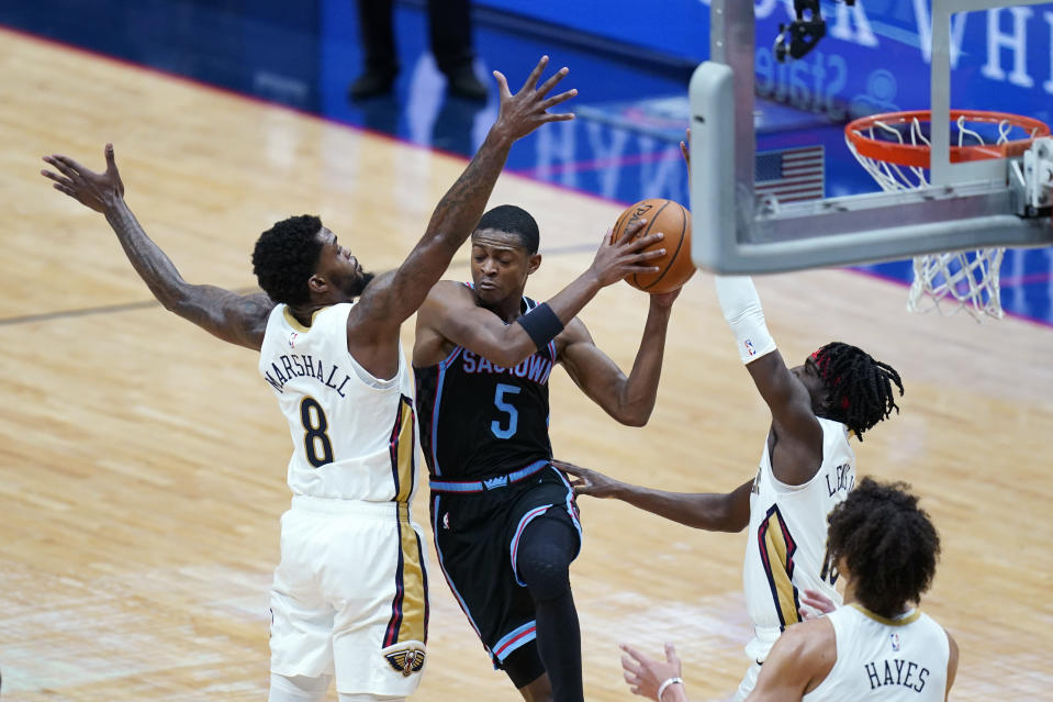 Sacramento Kings guard De'Aaron Fox (5) drives to the basket between New Orleans Pelicans forward Naji Marshall (8), guard Kira Lewis Jr. (13) and center Jaxson Hayes in the first half of an NBA basketball game in New Orleans, Monday, April 12, 2021. The Pelicans won 117-110. (AP Photo/Gerald Herbert)