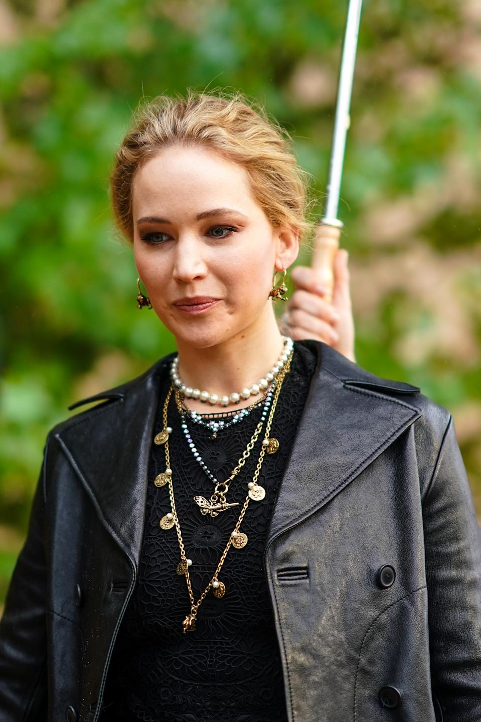 PARIS, FRANCE - SEPTEMBER 24: Jennifer Lawrence wears earrings, necklaces, a black lace crop top, a black leather jacket,  outside Dior during Paris Fashion Week - Womenswear Spring Summer 2020, on September 24, 2019 in Paris, France. (Photo by Edward Berthelot/Getty Images)