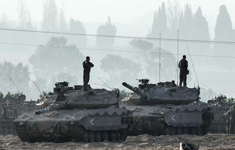 Israeli soldiers stand on Merkava tanks in an army deployment area near the border with the Gaza Strip, on July 8, 2014