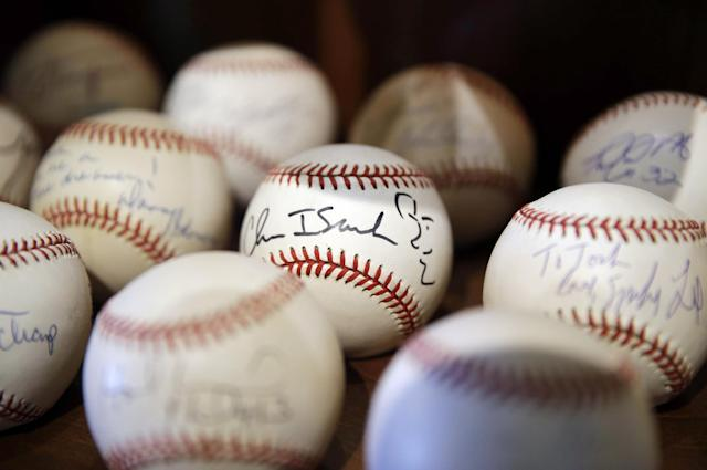 In this March 13, 2014 photo, a signed baseball with a self-portrait by rock musician Chris Isaak is shown in Dusty Baker's collection at his home in Granite Bay, Calif. Out of uniform for the first time since taking 2007 off between managerial jobs with the Cubs and Reds, Baker is not slowing down much from his pressure-packed days in the dugout. (AP Photo/Eric Risberg)
