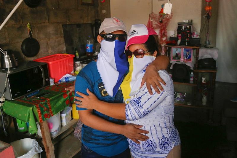 Opposition prisoner Jonathan Lacayo (L), embraces his mother at his house in Managua on June 10, 2019, both wearing masks for fear of reprisal attacks by supporters of President Daniel Ortega (AFP Photo/Maynor VALENZUELA)